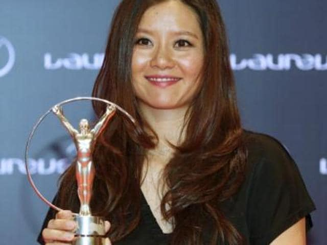Former tennis player Li Na poses for photographs with her award at the 2015 Laureus World Sports Awards.