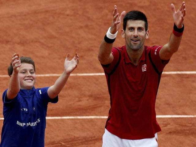 Serbia's Novak Djokovic (right) teaches a ballboy how to celebrate a victory after he defeated Spain's Roberto Bautista Agut during their fourth round match of the French Open tennis tournament at the Roland Garros stadium.