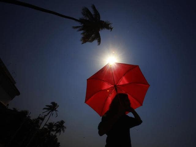 A man stands with an umbrella in the scorching heat at Dadar.