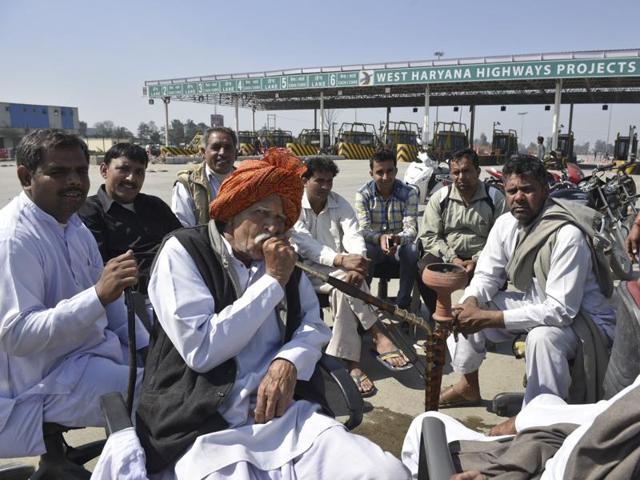 Jat quota agitation protestors sit on the Rohtak road in Sampla, near Rohtak on February 22, 2016.