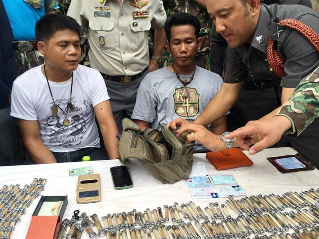A police officer, right, examines the belongings of two men arrested after attempting to remove tiger skin's and products from the