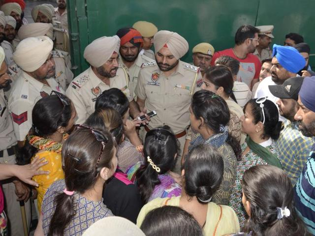 Police officials interacting with protesting parents outside a private school in Amritsar on Wednesday.