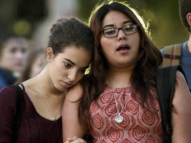 Catania Billalovos, left, holds onto Mireia Villanova, right, as they stand in front of a vigil for professor William Klug at the University of California, Los Angeles, Thursday.