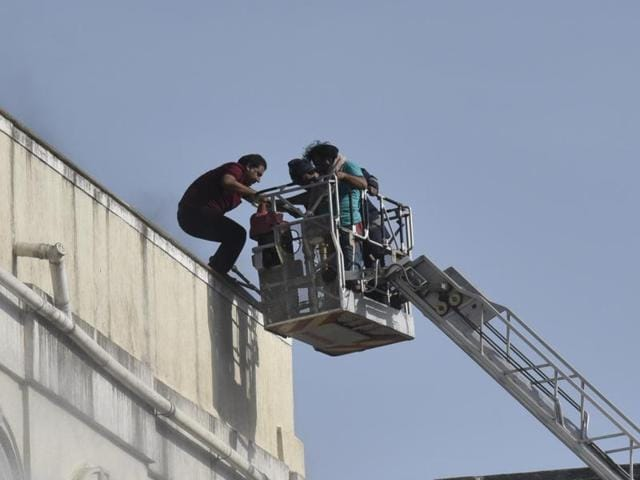 Three people were rescued from the burning building by fire brigade officials (top) as the efforts to douse the fire continued for hours.