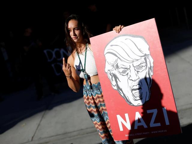 A demonstrator holds a sign in protest against Republican US presidential candidate Donald Trump outside his campaign event in San Jose, California.