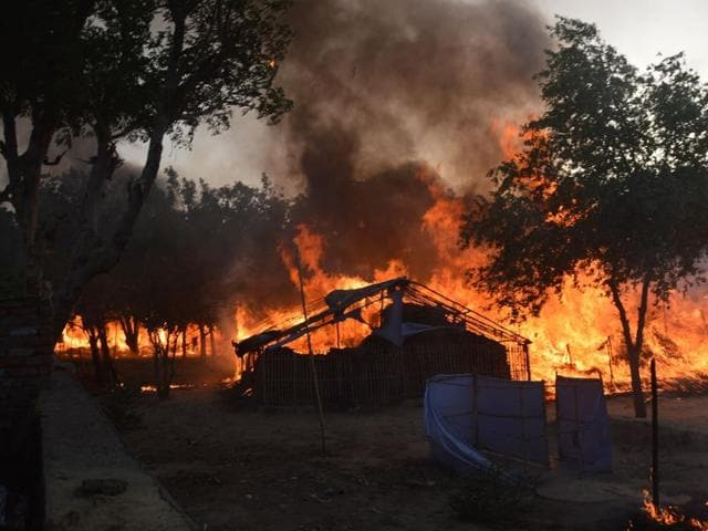 Former homes of the members of a sect burn following clashes with police during an eviction at the Jawahar Bagh park in Mathura on Thursday.