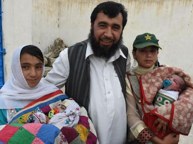 In this photograph taken on March 23, 2016, Pakistani man Sardar Haji Jan Mohammad Khilji poses with some of his children at his residence in Quetta.