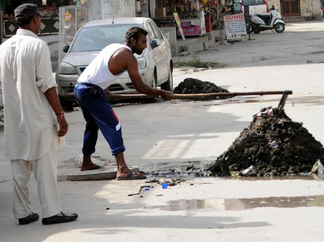 Municipal corporation workers clearing waste from a covered drain near Khalsa Mohalla in Patiala on Thursday.