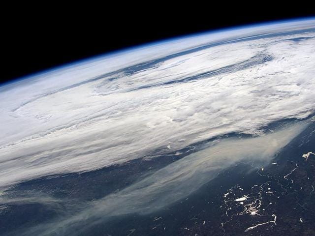 The smoke plume (bottom) from large wildfires in and around Ft McMurray, Alberta, Canada is seen in a picture taken by NASA astronaut Jeff Williams from the International Space Station May 11, 2016.