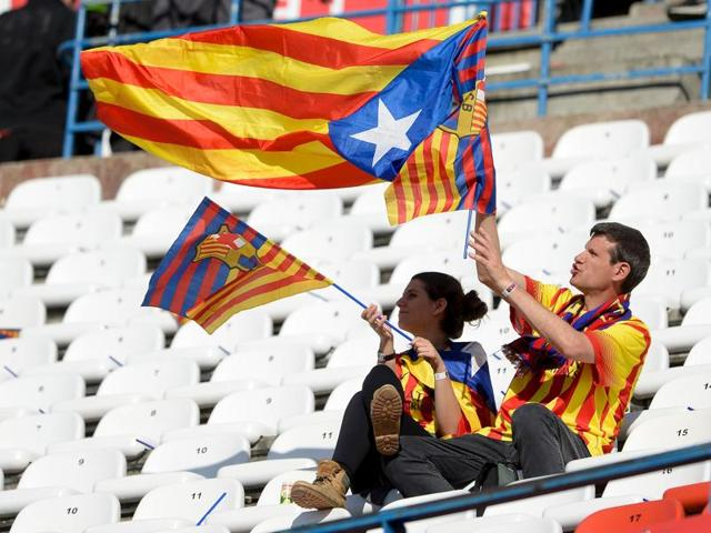 A supporter of FC Barcelona waves a