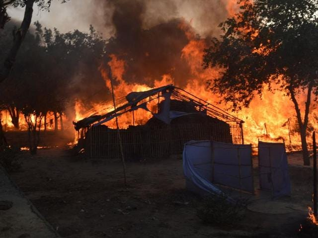 A fire burns after police attempted to evict thousands of followers of a cult  from Jawahar Bagh park in Mathura. Clashes between police and the followers left 24 people dead, including to police officers on June 3.  Police suspect cult leader Ram Vriksha Yadav may have died in the fire.