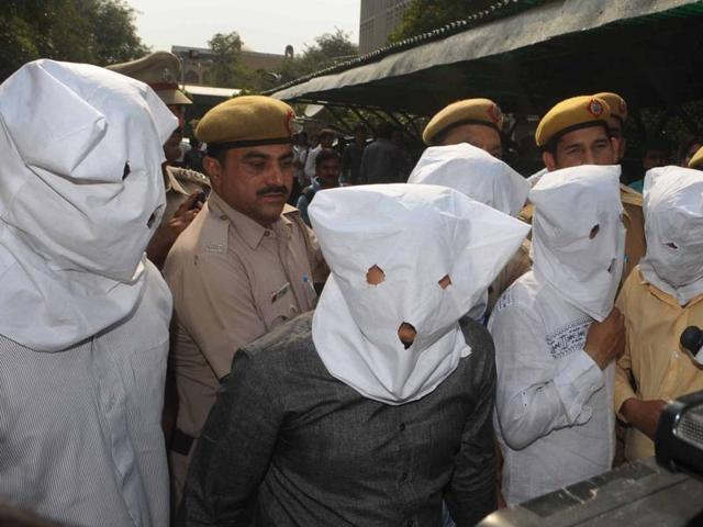 Police officials pose with suspected members of a kidney trading racket in Delhi.