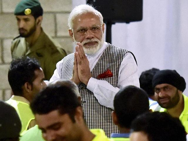 Prime Minister Narendra Modi greets Indian workers working in Doha at a camp in Qatar on Saturday.