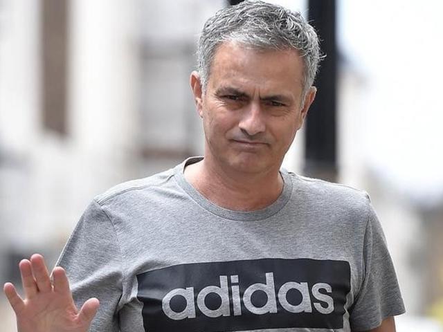 Jose Mourinho gestures as he walks towards his house in London, Britain.