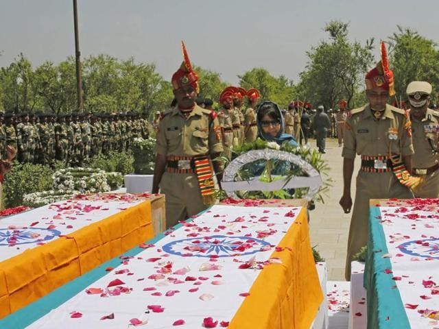 J&K chief minister Mehbooba Mufti, on the outskirts of Srinagar on June 4, 2016, lays a wreath on the coffins of three BSF personnel who were killed by militants a day before.