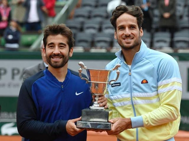 Feliciano Lopez, second left,, and Marc Lopez, left, hold their winners' trophy after defeating Bob Bryan, right, and Mike Bryan, in  the men's doubles final at the French Open on June 4, 2016 in Paris.