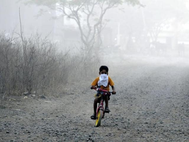 A child cycles near a trenching ground in Indore with his face covered to protect him from the smoke.