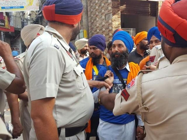 Police detaining youths who were seen distributing T-shirts of Jarnail Singh Bhindranwale at the Plaza Complex in Amritsar on Monday.