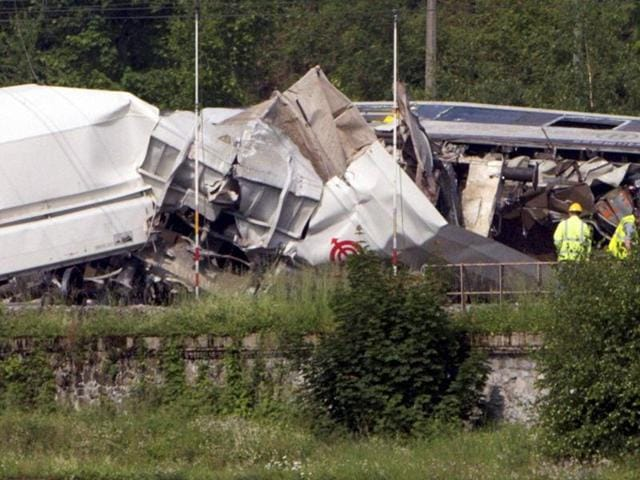 Investigators stand near the wreckage of a passenger and freight train after they collided in Hermalle-sous-Huy, near Liege, Belgium on Monday.