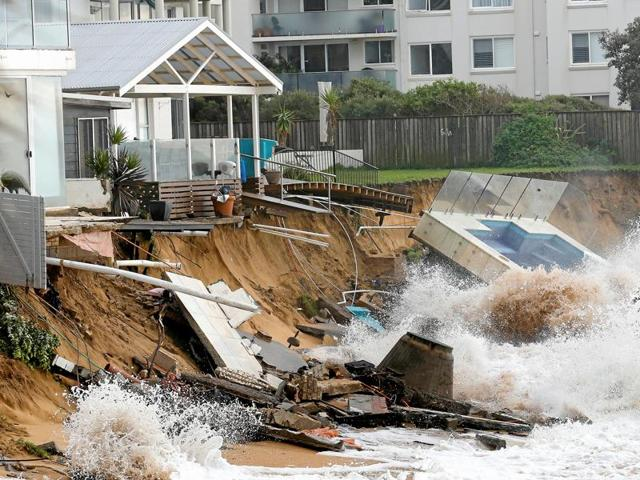 A wave crashes against a swimming pool and properties after they were damaged by severe weather, which brought strong winds and heavy rain to the east coast of Australia, at Collaroy beach in Sydney.