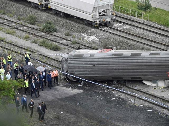 King Philippe of Belgium (C) and Belgian Prime Minister Charles Michel (C, right) visit the scene of a train collision between a freight train and a passengers train on the line between Liege and Namur.