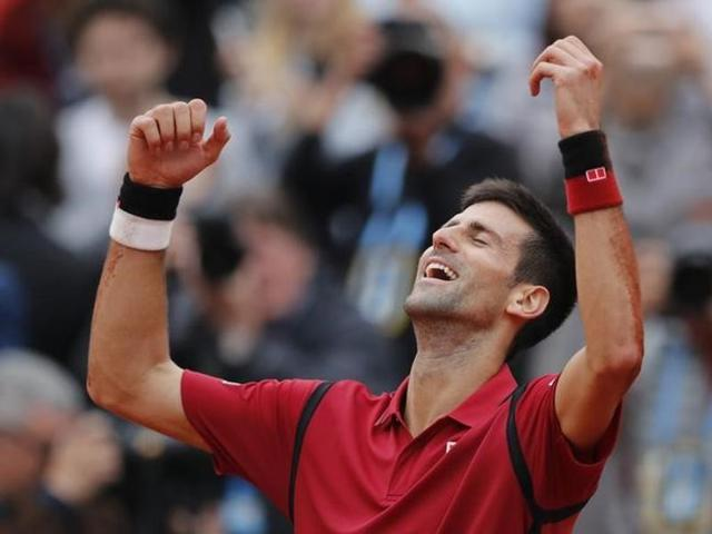 Serbia's Novak Djokovic poses with his trophy after winning the men's final match against Britain's Andy Murray at the Roland Garros French Tennis Open in Paris on June 5