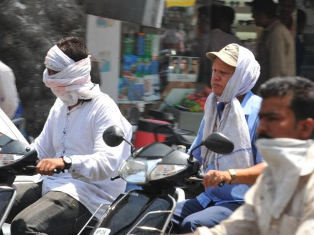 Commuters cover their face with cloth as day temperature rose to 44 degrees Celsius in Indore on Monday.