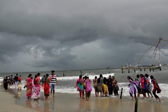 Girls enjoying in the Arabian sea against the backdrop of monsoon clouds in Kochi.