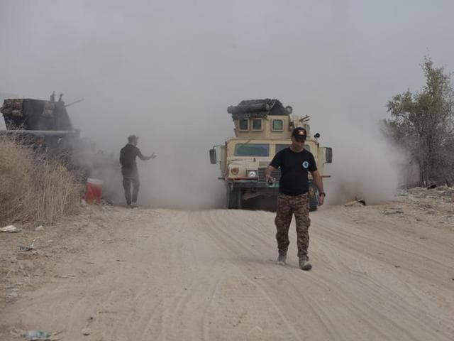 Iraq's elite counterterrorism forces move their vehicles on the front line in Fallujah on Sunday. Iraqi forces are pushing their way into the city to retake it from Islamic State militants.
