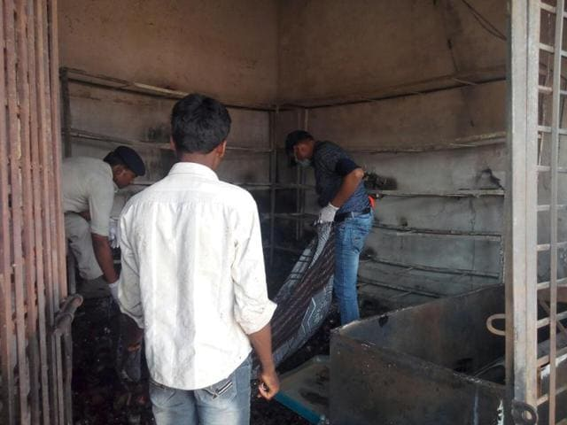 Cops investigating at the liquor shop that was burnt by a mob at village Temni in Balaghat.