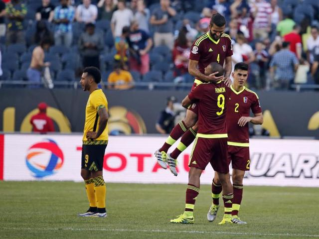 Venezuela's Oswaldo Vizcarrondo (4) jumps in to the arms of teammate Jose Salomon Rondon (9) as they celebrate a 1-0 win over Jamaica in a Copa America Centenario group C football match at Soldier Field in Chicago.