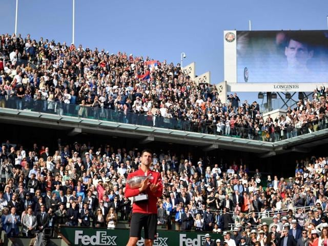 Winner Serbia's Novak Djokovic poses with the trophy after winning the men's final match at the Roland Garros 2016 French Tennis Open in Paris.