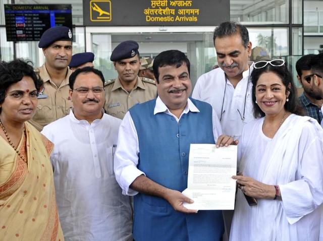 Union transport minister Nitin Gadkari receiving a representation from MP Kirron Kher at the Chandigarh international airport on Sunday.