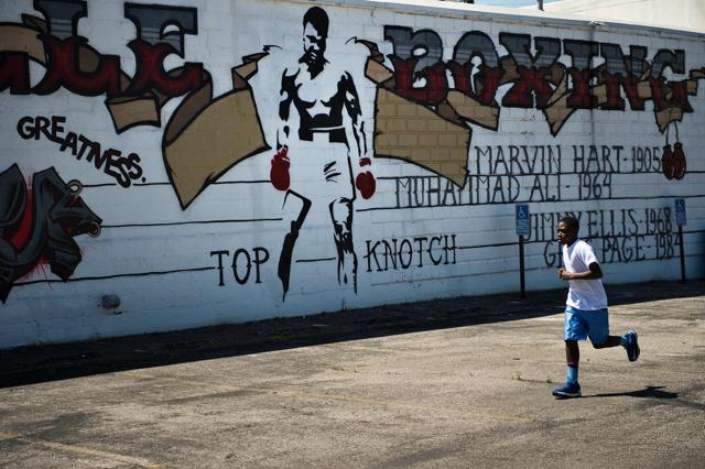 Employees of Joe's Pizza build a makeshift memorial to the late Muhammad Ali near a mural in New York.