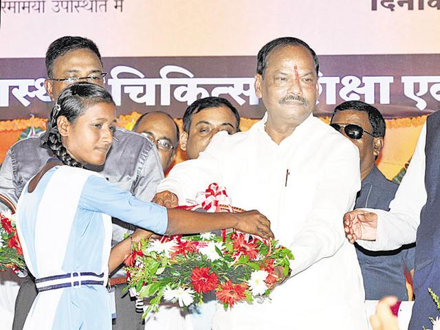 Chief minister Raghubar Das distributes sanitary napkins among girls after launching health schemes on the RCH premises in Ranchi on Monday.