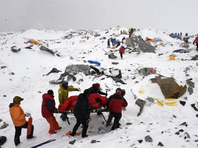 File photo from April 2015 shows rescuers using a makeshift stretcher to carry an injured person after an avalanche triggered by an earthquake flattened parts of Everest Base Camp.