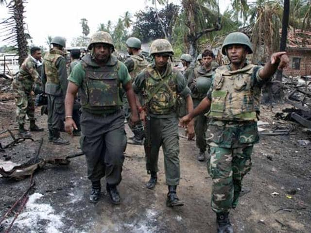 In this handout photograph received from the Sri Lankan Ministry of Defence on May 18, 2009, government soldiers inspect the area inside the war zone near Mullaittivu on May 17, 2009, when they helped evacuated the last of the Tamil civilians from the area.