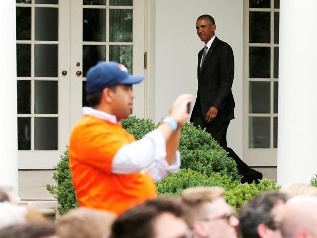 A Denver Broncos fan takes pictures of the team as US President Barack Obama walks back to the Oval Office (rear) after welcoming the Broncos for a reception in honor of their NFL Super Bowl football championship, in the Rose Garden of the White House in Washington.