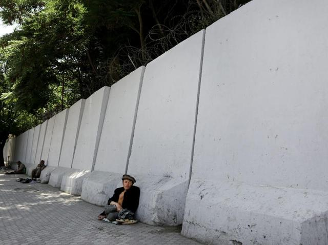 An Afghan bigger sits in front of blast walls installed to cordon off the ministry of communications in Kabul.