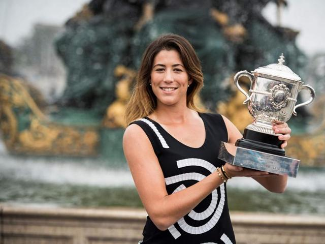 Spain's Garbine Muguruza poses for photographers with her trophy one day after winning her women's final match against Serena Williams at the Roland Garros 2016 French Tennis Open.