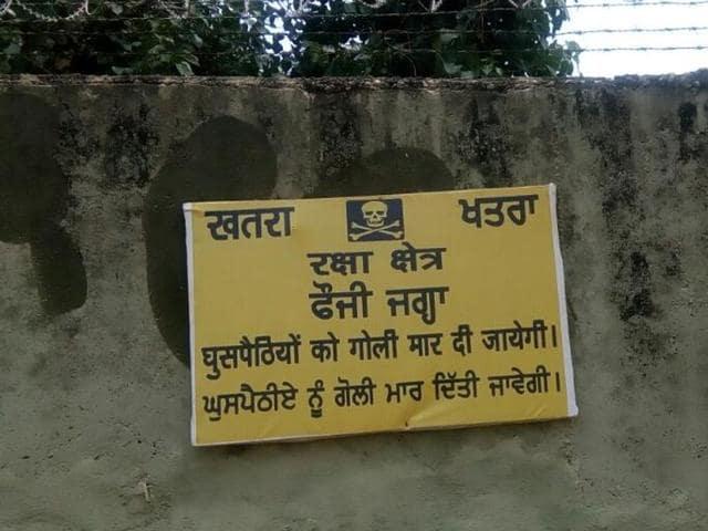 Wall of Pathankot Air Force Station bearing a warning message.