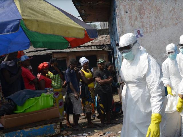This file photo shows a man walking past an Ebola campaign banner with the new slogan
