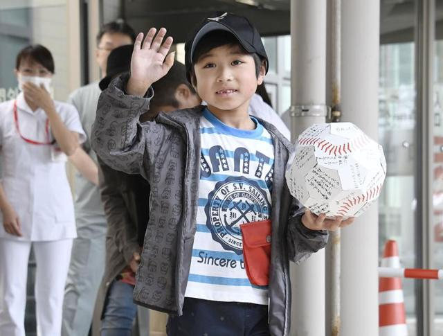 Yamato Tanooka, who was found after being abandoned by his parents as punishment in a forest, waves as he leaves a hospital in Hakodate on the northern island of Hokkaido.o News via AP) JAPAN OUT, MANDATORY CREDIT