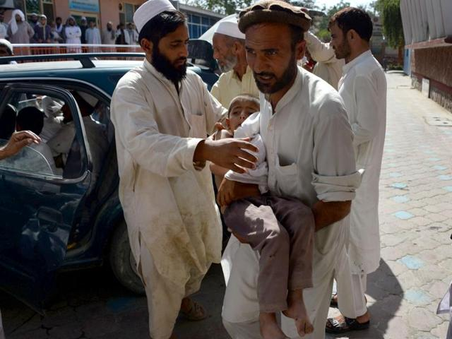 An Afghan volunteer carries a wounded child following an explosion inside a mosque in the Rodat district of Nangarhar province on June 10, 2016.