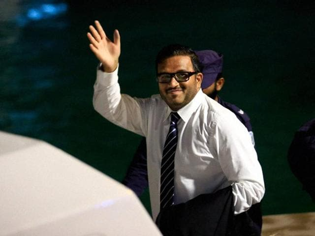 Former Maldives vice-president Ahmed Adeeb waves to the media before he boards a police speed boat in Maldives.