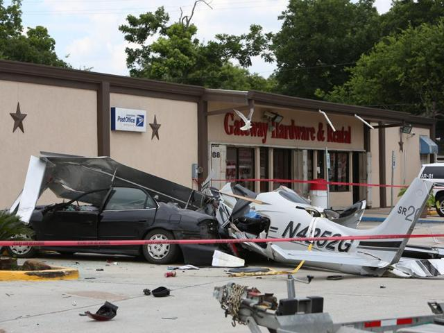 The wreckage of a small plane that crashed into a car in a parking lot near a Houston airport.