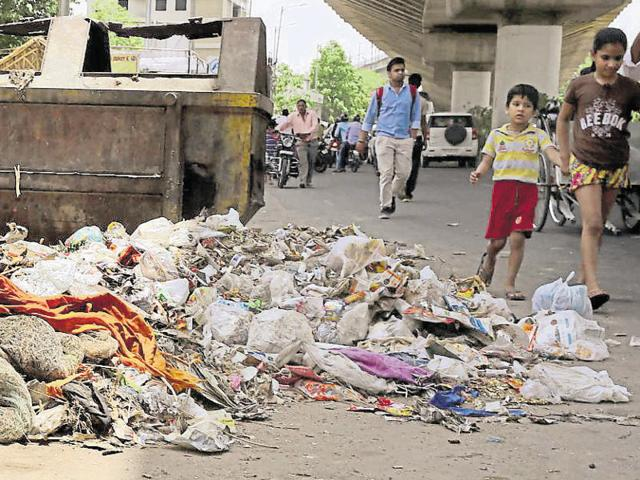 A man covers his nose as he crosses MI Road littered with waste.