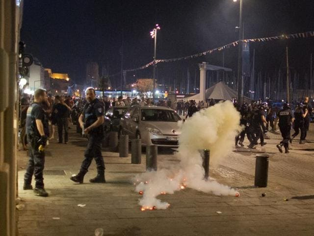 Teargas smokes as police and football fans gather in downtown Marseille, France, early on June 10, 2016. Trouble flared outside an Irish pub in the Old Port of the southern city just before midnight Thursday, apparently between English fans drinking there and some local people.