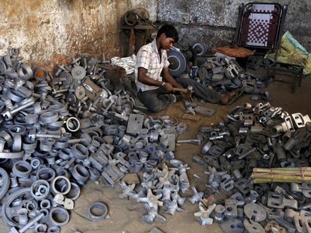 A worker separates casting joints of gearboxes inside a small-scale automobile manufacturing unit in Ahmedabad.