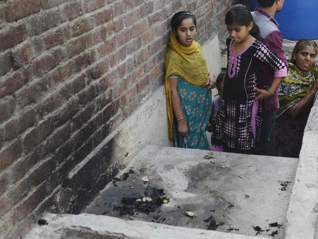 Residents stand at the site where a teenager was burnt alive by her mother in Lahore on June 8, 2016.